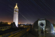 Star trails on pictured behind a telescope and Campanile at UC Berkeley