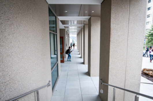 Students walking into physics building in daytime